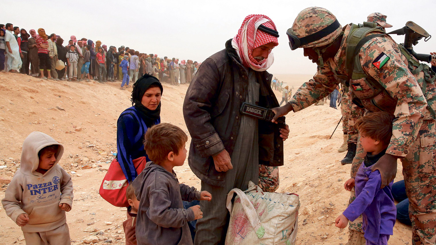 A Jordanian soldier scans newly arrived Syrian refugees as they wait to cross the border - KHALIL MAZRAAWI/AFP/Getty Images