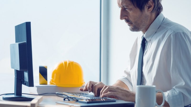 civil engineer using laptop with hard hat next to him