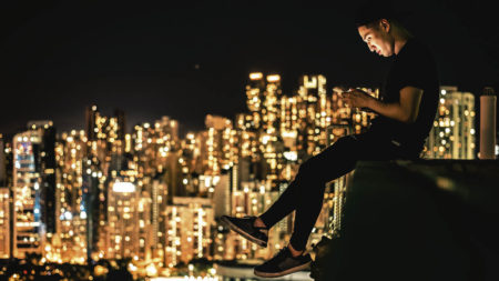 A young man looking at a smart phone overlooking the city