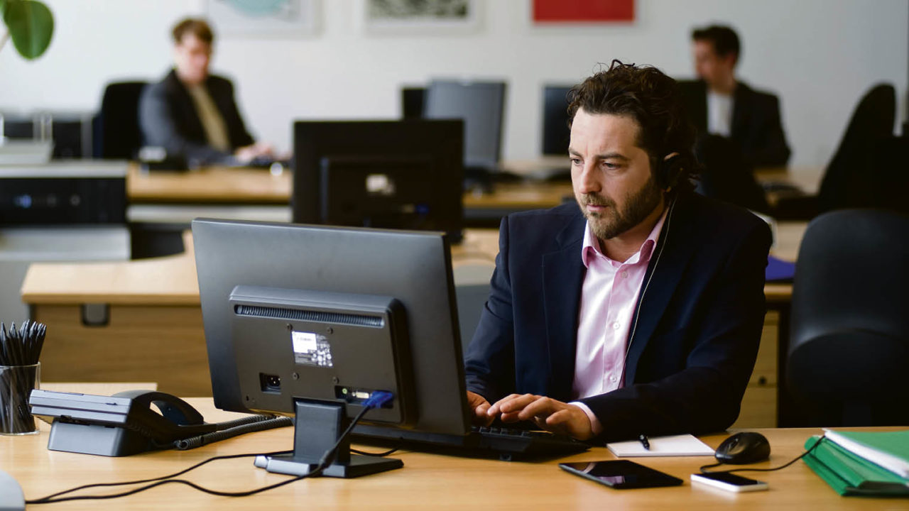 Male professional in an office on a computer