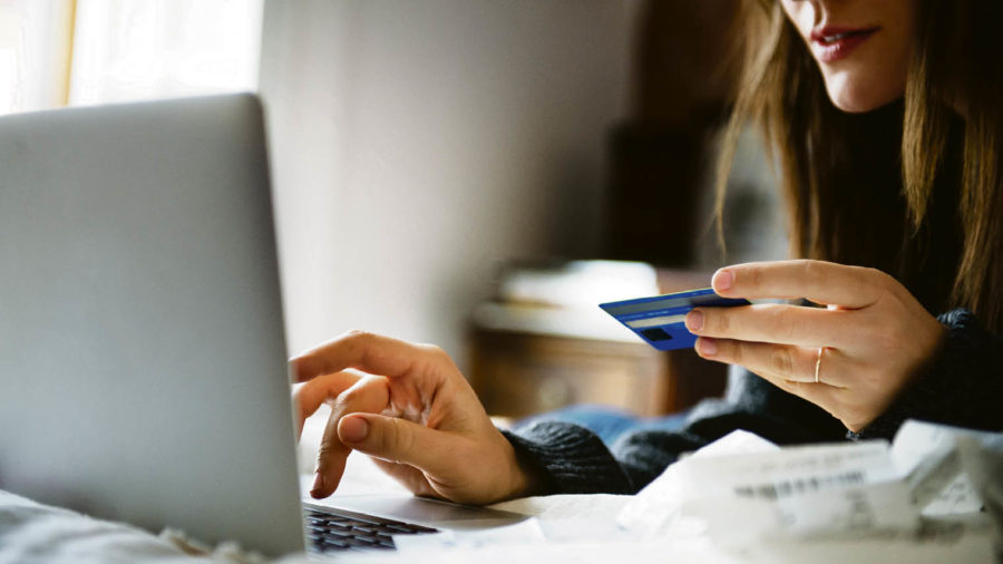 Woman entering card details to her laptop