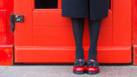 Woman wearing red shoes in front of a red door