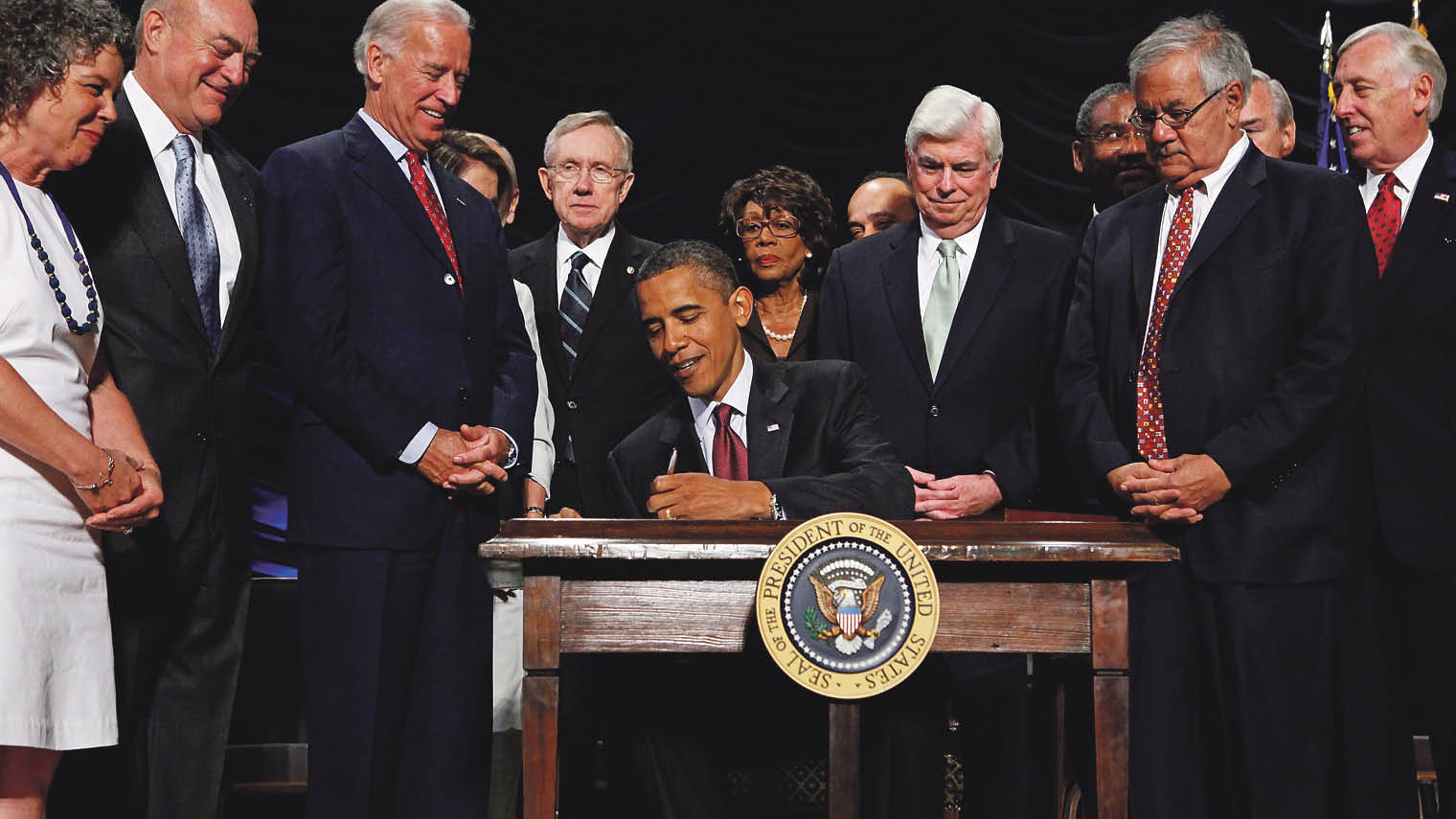 Barack Obama signing the Dodd–Frank Wall Street Reform and Consumer Protection Act into law in July 2010