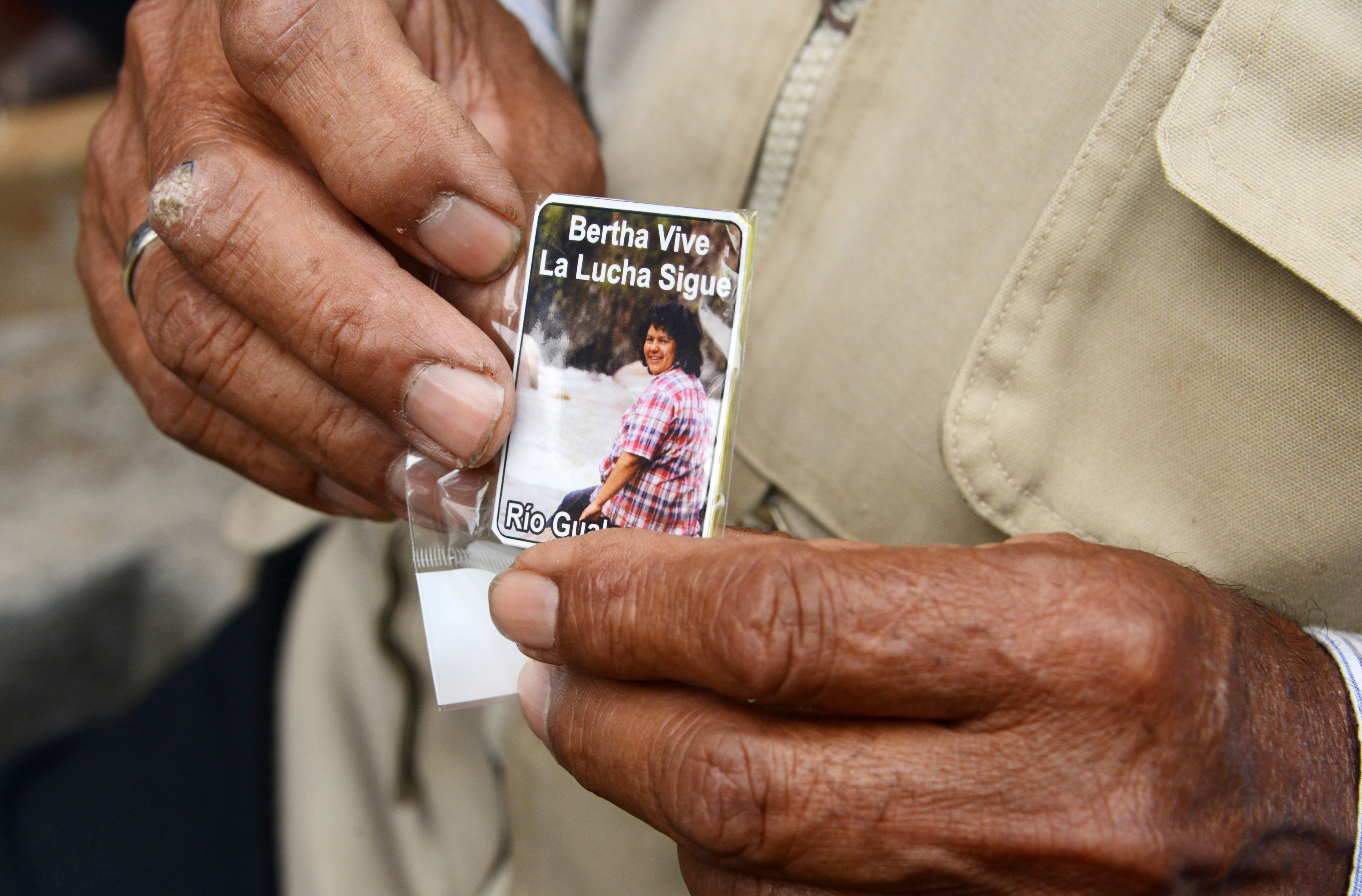 man holds a card bearing a picture of Cáceres, which reads 'The fight continues'