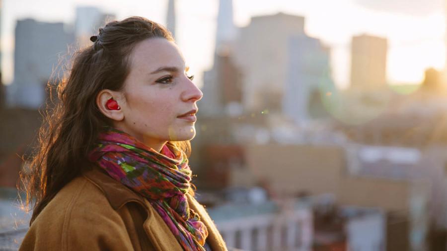 Young woman wearing pilot earplug translator