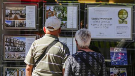 Elderly couple looking in estate agent window