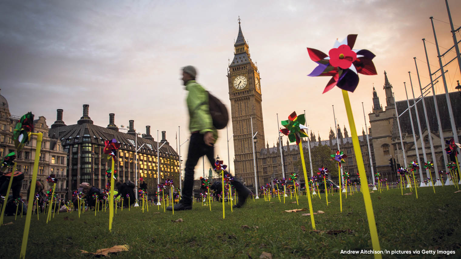 Person walking past Westminster with pinwheels on the grass