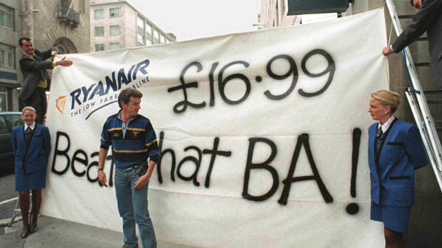 Ryanair's chief executive Michael O'Leary in front of a banner outside rival British Airways' travel shop in 1998