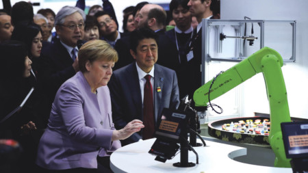 German and Japanese leaders Angela Merkel and Shinzo Abe watch a robotic arm serving sushi at the CeBIT 2017 tech fair in March