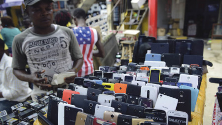 A phone vendor beside his stand at Computer Village, a consumer tech market in Lagos; the proliferation of smartphones in emerging markets such as Nigeria is generating massive amounts