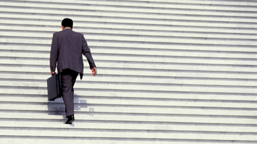 Man in suit walking up stairs