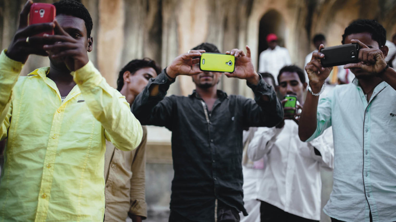 Men in India with their smart phones