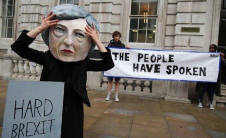 "A demonstrator wears a mask depicting Britain's Prime Minister and leader of the Conservative Party Theresa May, poses with a mock gravestone bearing the words ""Hard Brexit, RIP"", during a protest photocall near the entrance 10 Downing Street in central London on June 9, 2017 as results from a snap general election show the Conservatives have lost their majority."