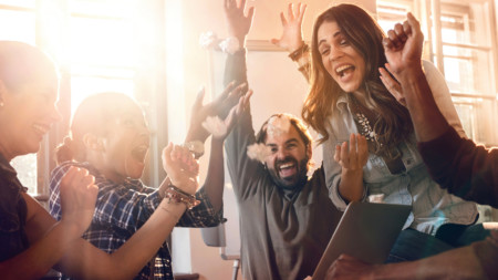 Group of cheerful people celebrating their business achievement in the office. They are screaming and throwing crumpled papers.