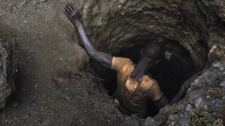 Mining employee, or creuseur, descends into a copper-cobalt mine in Kawama, Democratic Republic of the Congo, where conditions are dangerous with little to no safety equipment or structural support in the tunnels; they are paid on average $2 to $3 a day