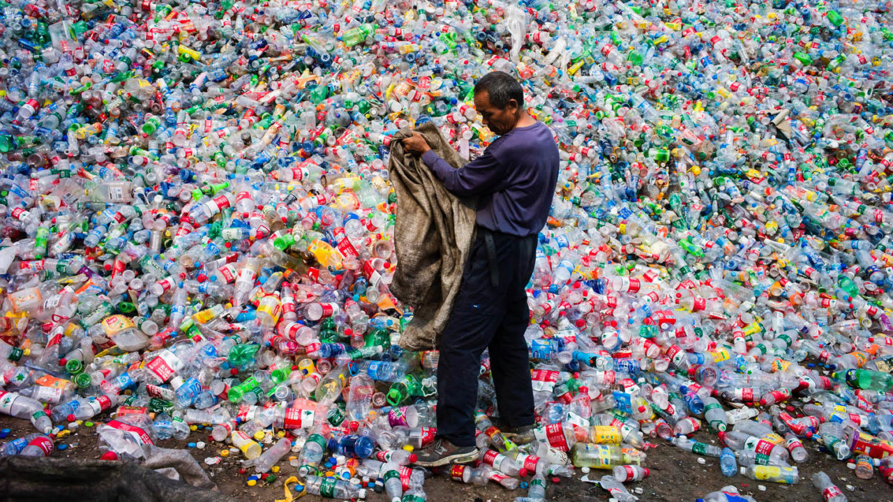 Chinese labourer sorting plastic bottles for recycling at a plant on the outskirts of Beijing