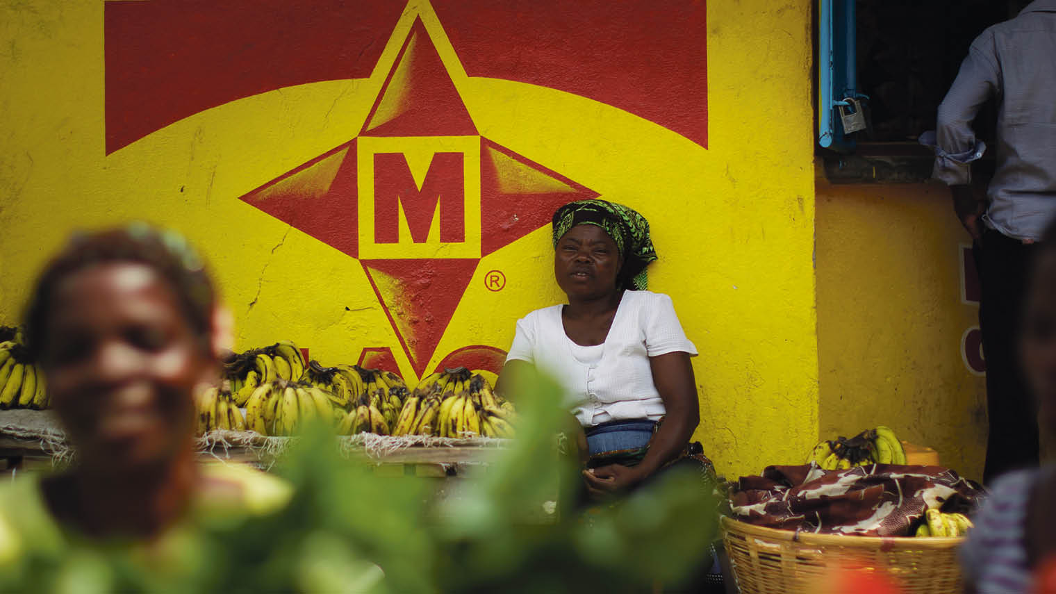 Lady sits in market by Maggi food logo Africa