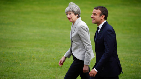 Theresa May and Emmanuel Macron walking