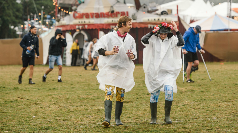 Two people at Bestival music festival dressed for rain