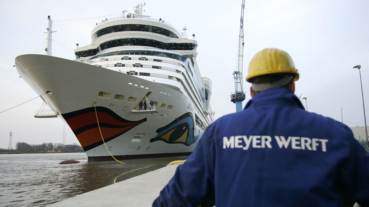 A worker with Meyer Weft on their overalls watches a cruise liner