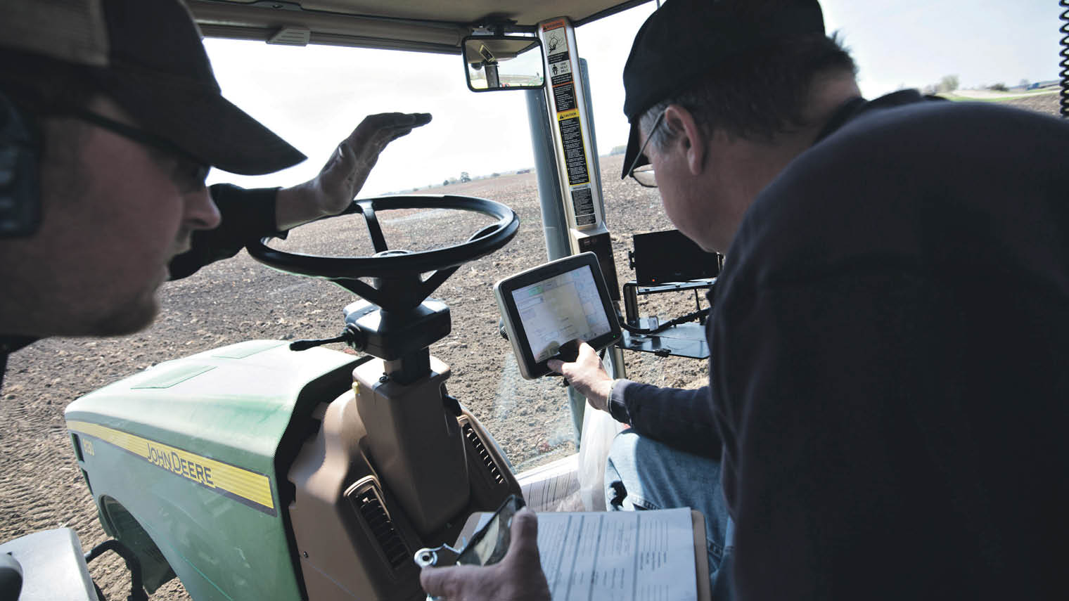 Farmers using tablet in tractor
