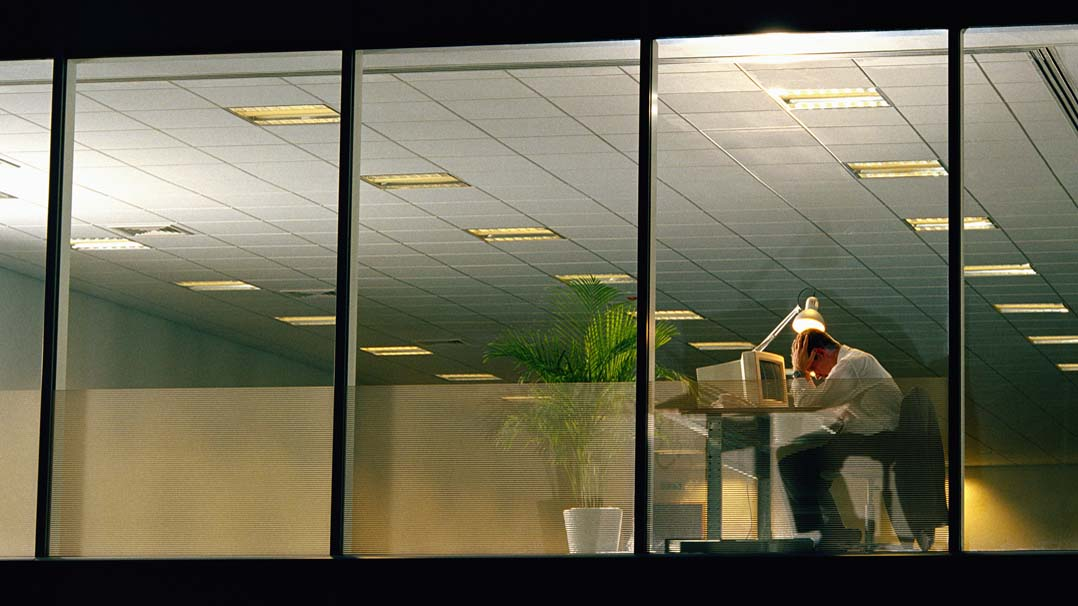 Man in office late at night, head in hands