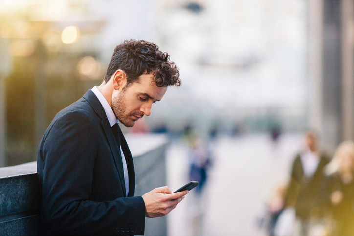 Businessman reading smartphone texts on city street