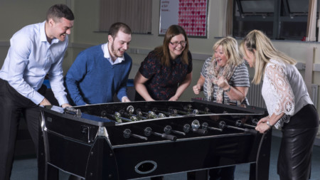 Employees of South Liverpool Homes playing table football