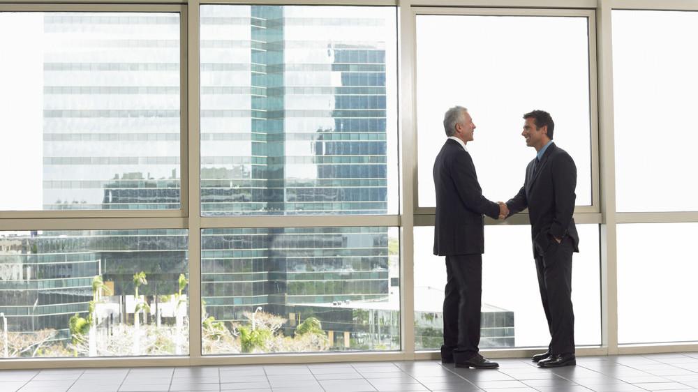 Two business men shaking hands in window