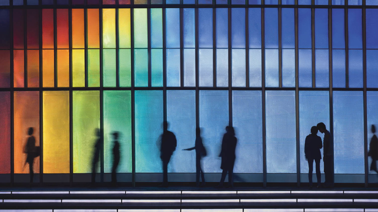 Rainbow building with people in front
