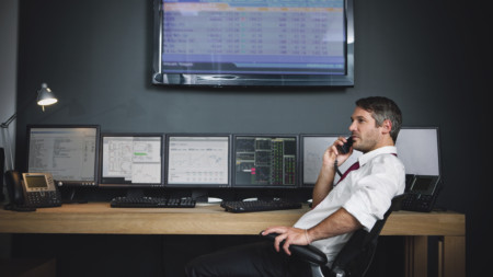 stock broker on the phone at desk