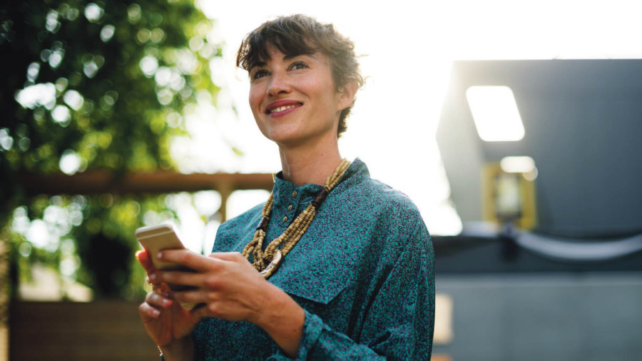 Woman smiling holding smartphone
