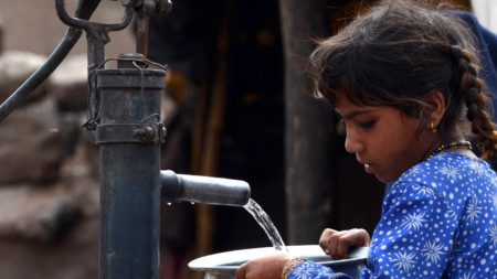Young girl filling a pot from a water hand pump in Lahore, Pakistan