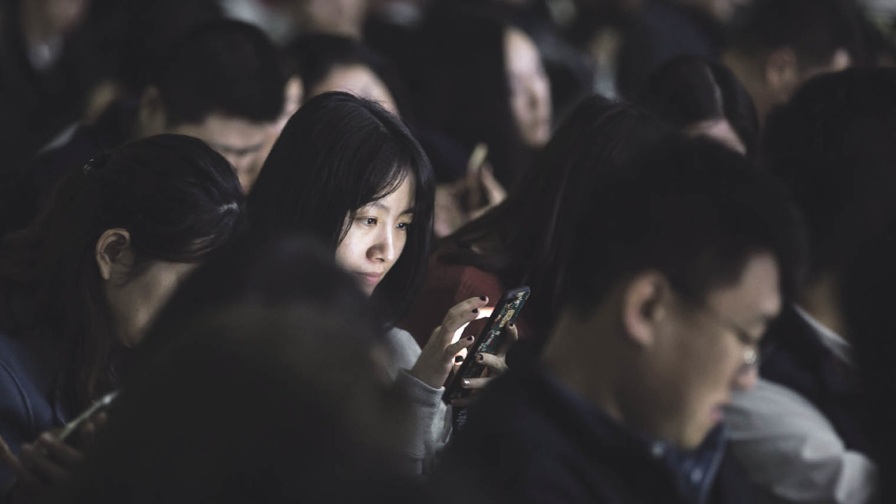 Woman using phone in crowd