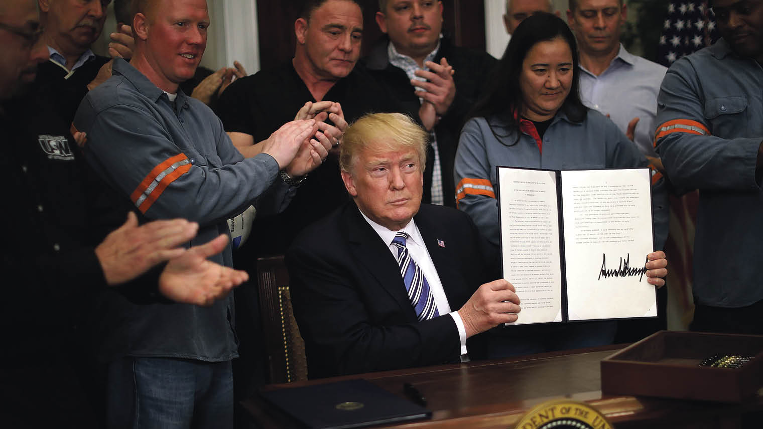 Donald Trump holding the Section 232 Proclamation on steel imports