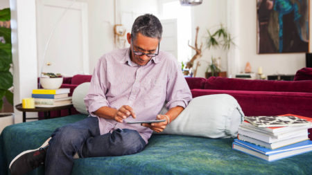 Man sitting on couch using tablet