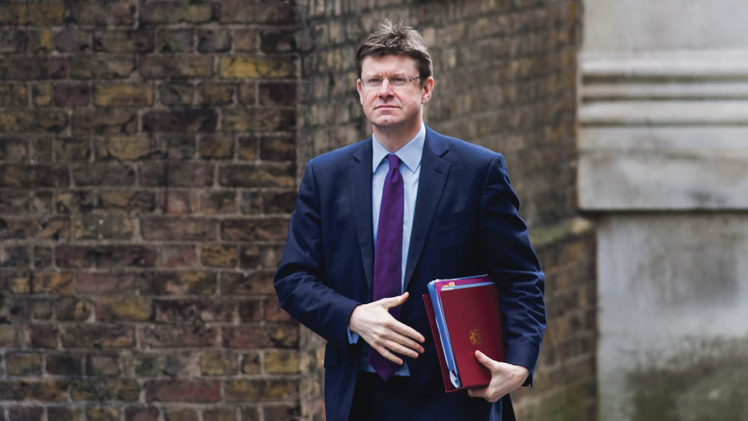 Greg Clark Secretary of State for Business, Energy and Industrial Strategy in suit holding folder