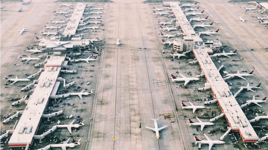 bird's eye view shot of many aeroplanes parked in rows on airfield