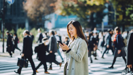 business woman on looking on phone in crowd of people travel chatbots