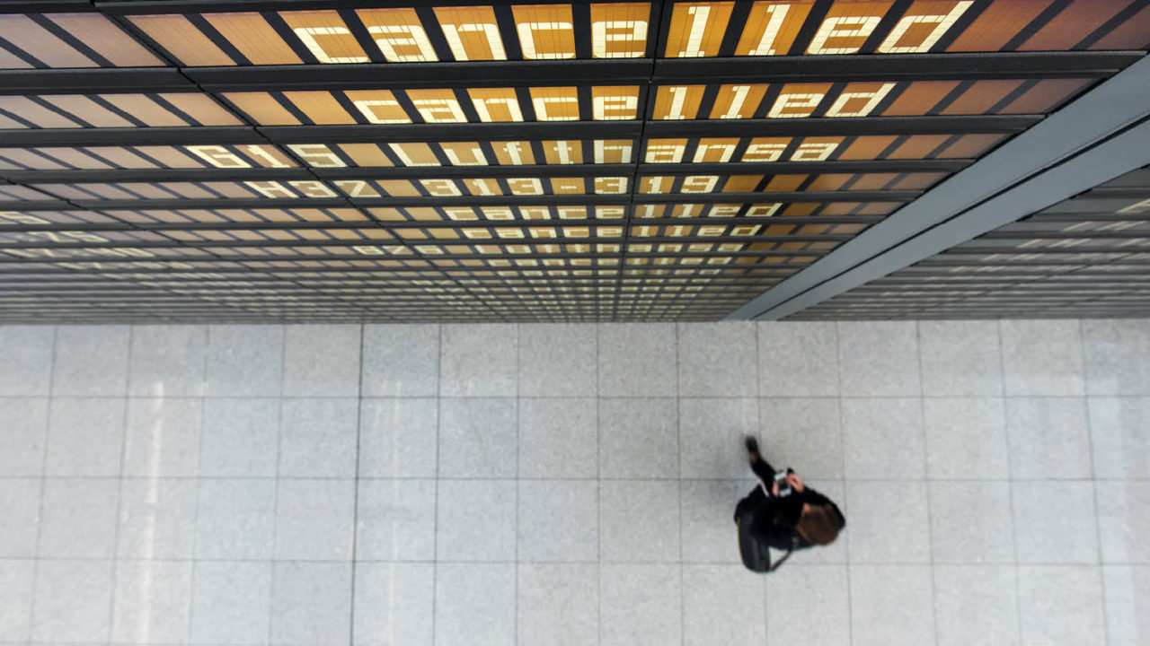 Bird's eye view of departure boards with person standing below assessing travel risk