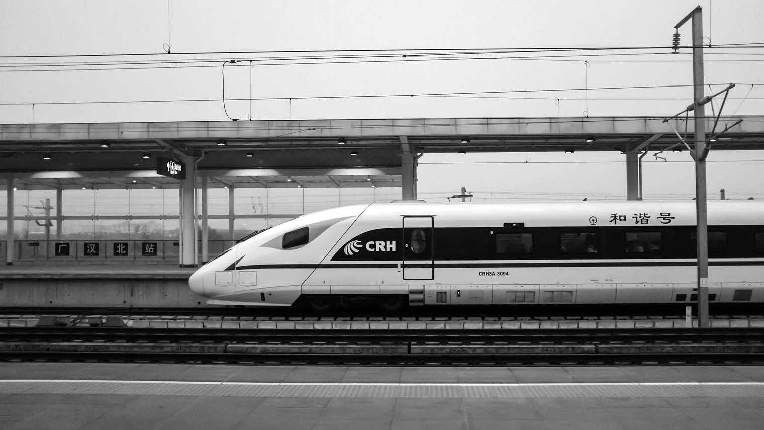 black and white super train at platform in station
