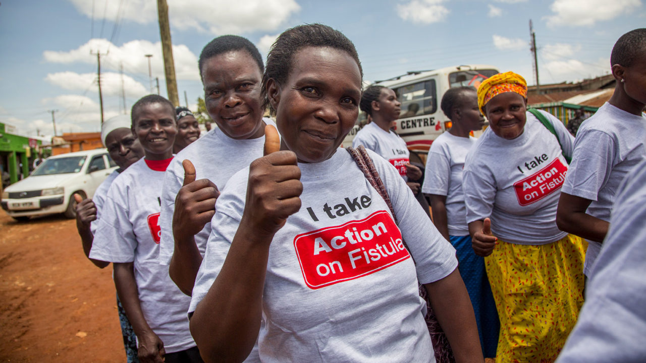 people wearing Action on Fistula t-shirts giving thumbs up