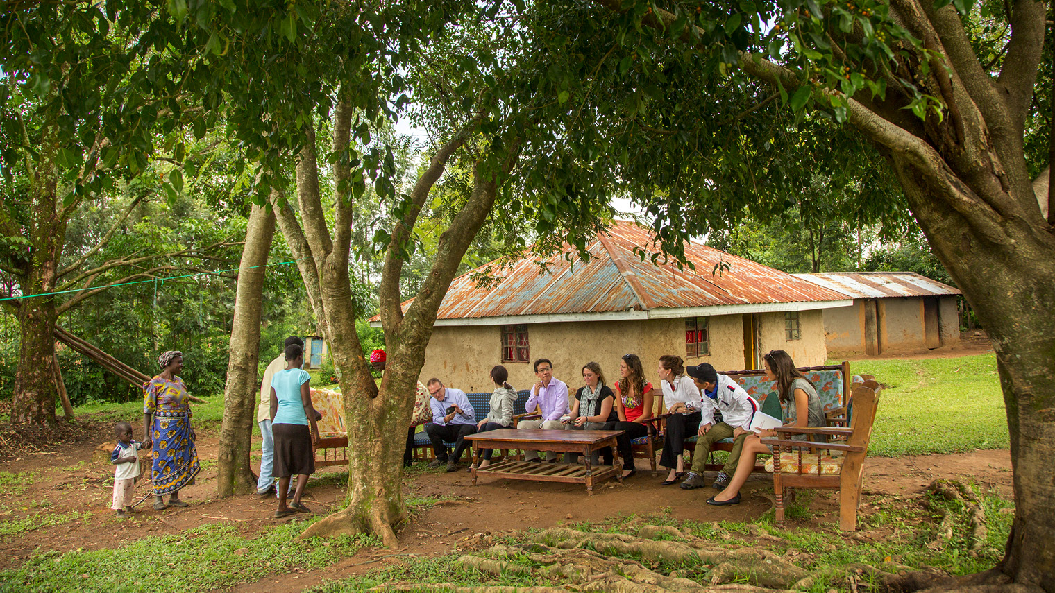 people gathered under trees outside house in Kenya