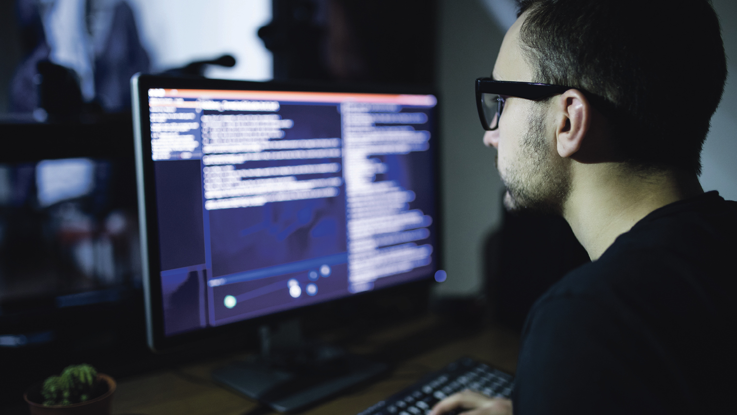 man looking at screen with code on it