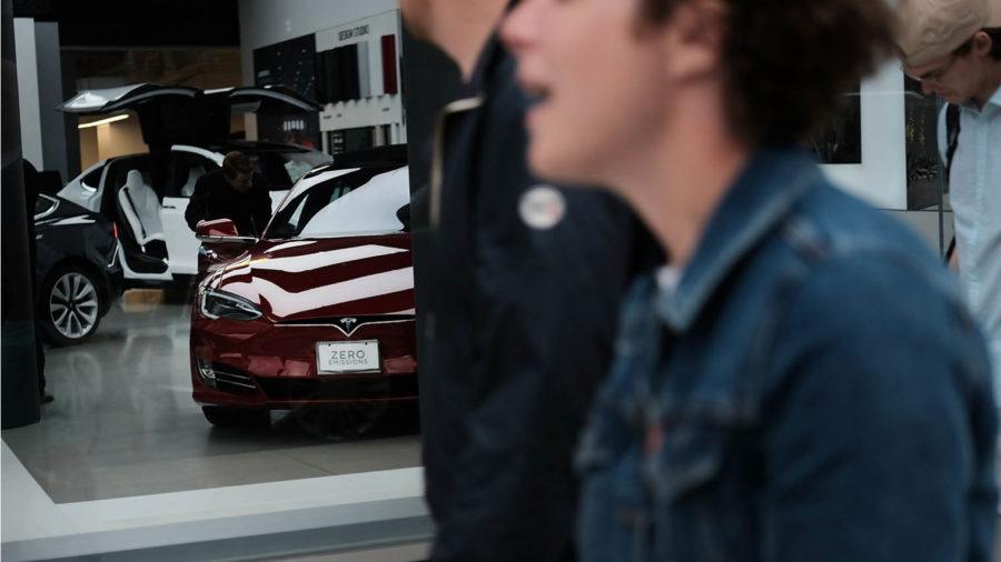 people walking past car showroom, car brand visible