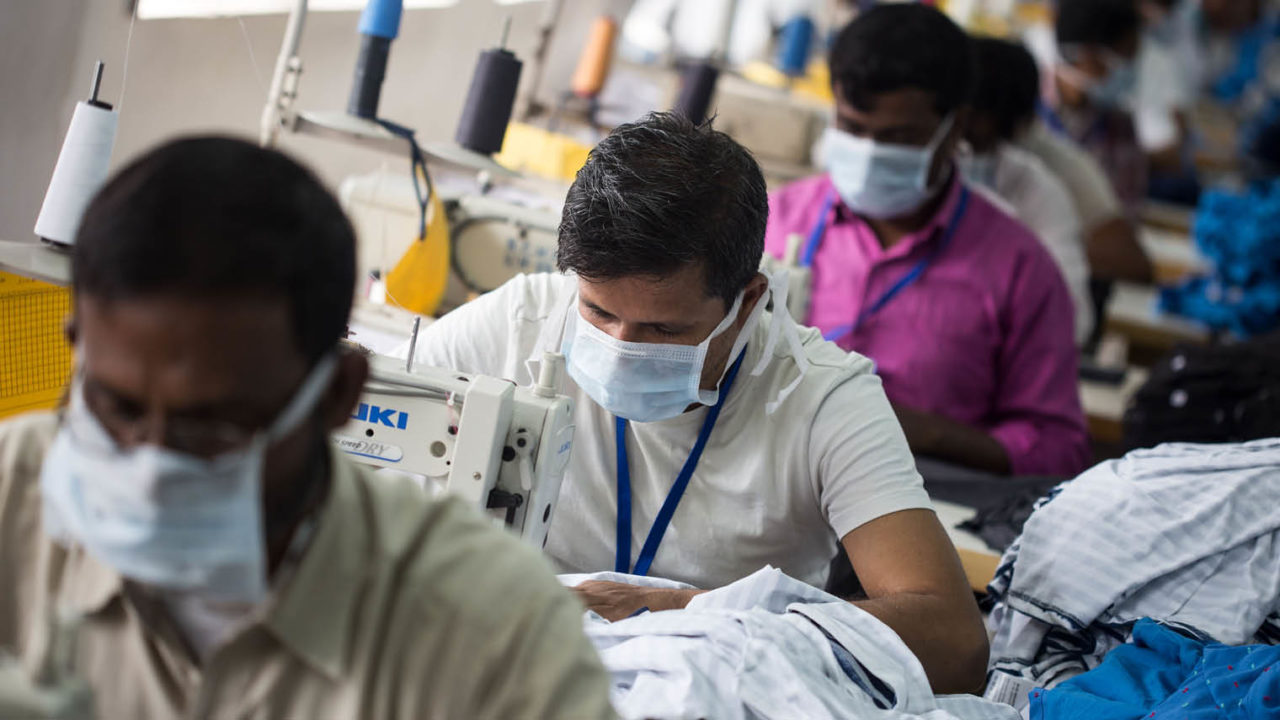 people sewing in factory, wearing face masks