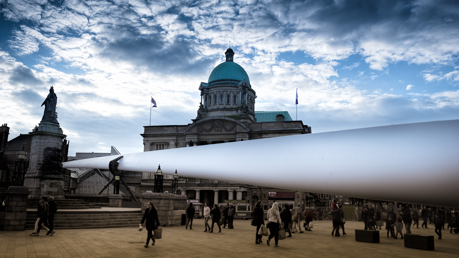 Siemens wind turbine blade in front of domed building clouds in sky
