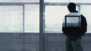 Man by window with blinds