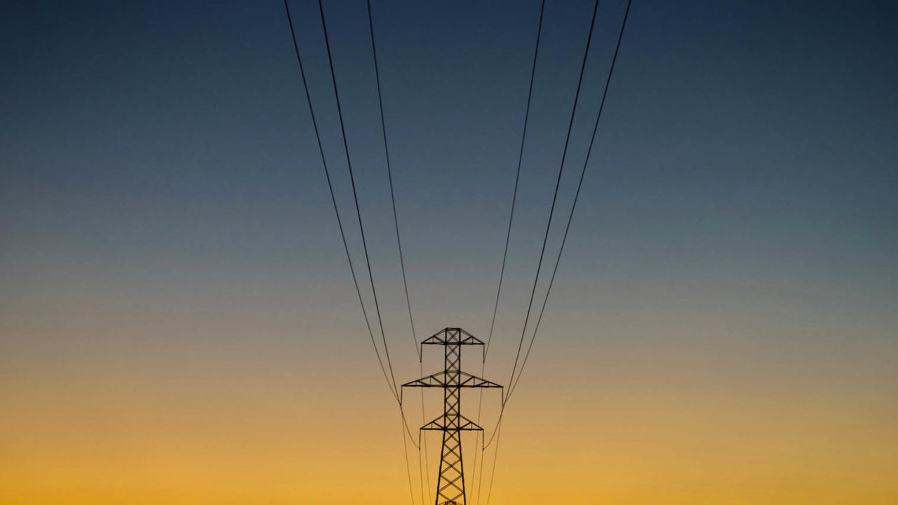 Electricity tower silhoutted against sky