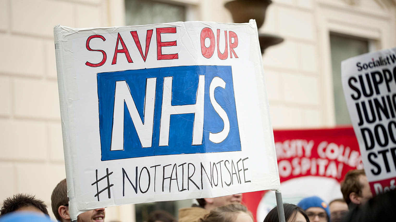 Save our NHS placard held above crowd